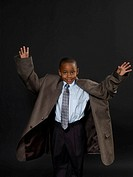 Boy 5-7 wearinjg suit and topcoat, raising arms