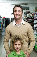 Father and son 6-8 in supermarket, smiling, portrait
