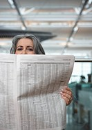 Mature businesswoman sitting in airport reading newspaper