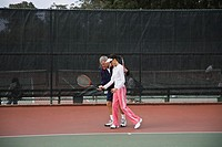 Mature man teaching mature woman how to play tennis, side view