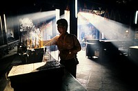 Hong Kong, male burning incense inside dark temple with sunrays filtering in windows