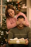 Woman covering husband´s eyes from Christmas present