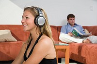 Man reading on sofa and woman listening to headphones indoors