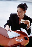 Businesswoman using laptop while drinking coffee