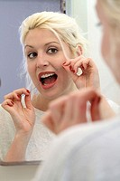 Young woman flossing in front of a mirror in bathroom