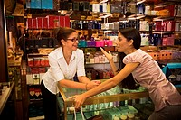 Woman chatting with beauty consultant in shop