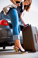 Young woman unloading luggage from car