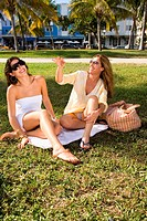 Two women sitting on blanket on grass
