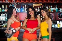Three waitresses standing in front of bar counter