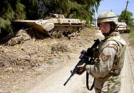 OPERATION IRAQI FREEDOM - Staff Sgt. Brandon Storey secures a road next to a destroyed Iraqi armored-personnel carrier during a training mission near ...