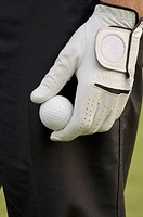 Man with sports glove holding golf ball