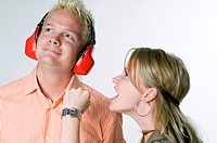 Girlfriend shouting at boyfriend who is wearing headphones