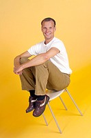 Man smiling at the camera while sitting on a stool
