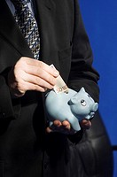 Businessman putting money into piggy bank