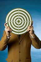 Businessman holding a dart board over his face