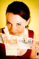 Woman posing with banknotes hanging on a clothes line