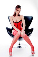 Woman in black and red corset sitting on chair