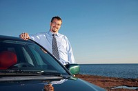 Businessman posing beside his car