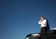 Businessman beside his car, holding his jacket while talking on the mobile