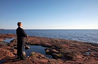 Businessman standing on the rocks holding a golf club