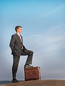 Businessman standing with his leg stepping on his briefcase