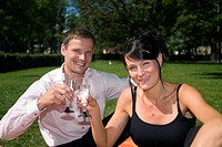Couple having a toast in the park