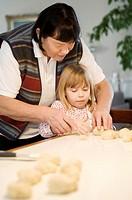 Grandmother assisting granddaughter in baking