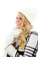 Woman in winter clothing smiling while looking away