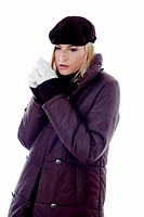 Woman in winter clothing staring blankly at a space