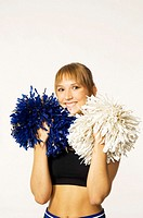 Teenage girl with pom-poms smiling at the camera (thumbnail)