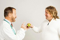 Doctor giving patient a green apple (thumbnail)