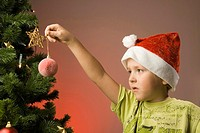 Boy with santa hat holding Christmas ornament (thumbnail)
