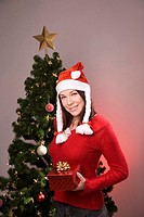Teenage girl with santa hat posing in front of christmas tree
