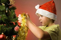 Boy decorating Christmas tree with festoon