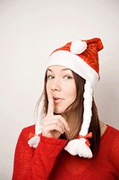 Teenage girl with santa hat showing hushing sign