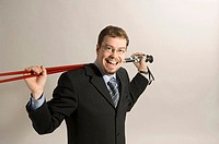 Businessman holding ski poles on his shoulder