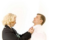 Angry businesswoman pulling businessman's shirt