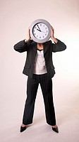 Businesswoman posing with a clock as her face