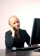 Businesswoman on the mobile while typing on the keyboard