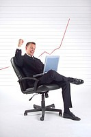 Businessman with laptop and line chart indicating revenue increase