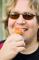 Man with sunglasses smiling while eating wild mushroom