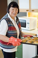 Senior woman with a tray of freshly baked buns