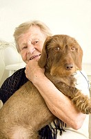 Senior woman posing with pet dog in her arms