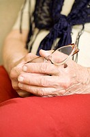 Senior woman sitting while holding her reading glasses