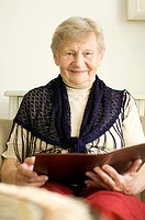 Senior woman smiling at the camera while holding a book