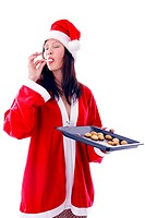 Woman eating cookies while holding freshly baked cookies in a tray