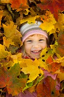 Girl with autumn leaves covering her