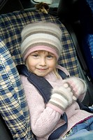 Girl in winter clothing sitting on car seat