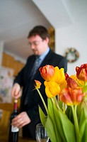 Businessman opening a bottle of wine, focus on flowers