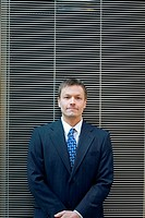 Businessman posing in front of the camera with window blinds as background